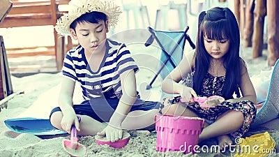 Crianças asiáticas felizes que jogam a areia na praia vídeos de arquivo
