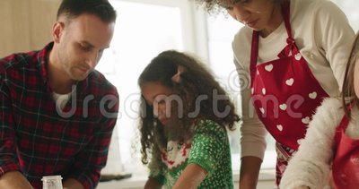 Crianças cozinhando biscoitos com ajuda de pais vídeos de arquivo