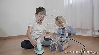 Crianças curiosas brincam com objetos perigosos, pequenos irmãos estudando ferro elétrico e soquete sentados no chão filme