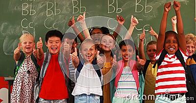 Crianças de sorriso que mostram os polegares acima na sala de aula