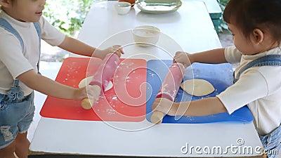 Crianças felizes preparando massa para pizza caseira na cozinha, enrolar massa com pino rolante e farinha na mesa Divertimento fa vídeos de arquivo