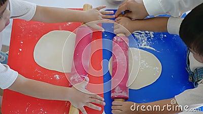 Crianças felizes preparando massa para pizza caseira na cozinha, enrolar massa com pino rolante e farinha na mesa Divertimento fa filme