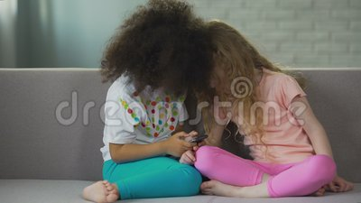 crianças Multi-étnicas que sentam-se no sofá e que jogam no smartphone, tecnologia moderna video estoque