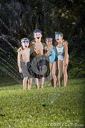 Crianças que riem e que shouting pelo sistema de extinção de incêndios do gramado