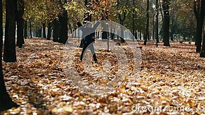 A crian?a joga as folhas amarelas no parque do outono O rapaz pequeno feliz que joga com as folhas de outono, jogando sae no movi filme
