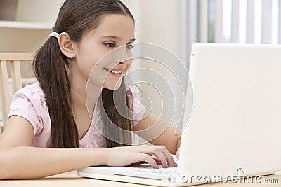 Criança da menina que usa o computador portátil em casa