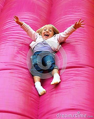 Criança feliz que joga na corrediça