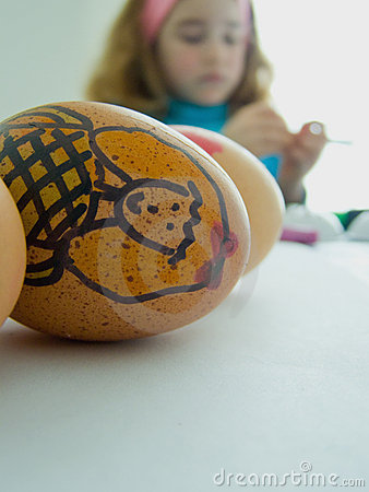 Criança que decora ovos de Easter