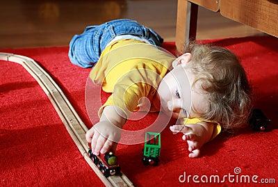 Criança que joga com trens em casa