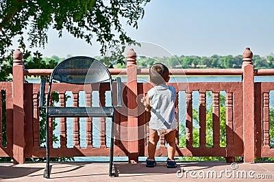 Criança que olha o rio