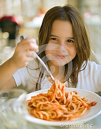 Criança que tem o espaguete