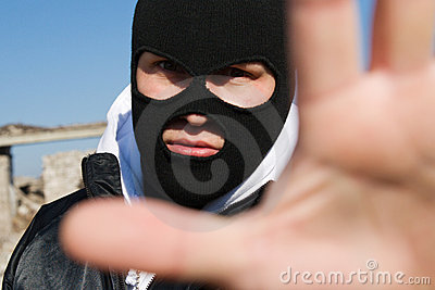 Criminal holding his hand in stop gesture