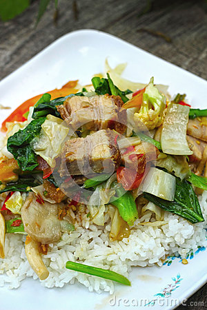 Crispy roasted  pork stir fry with vegetables and rice.