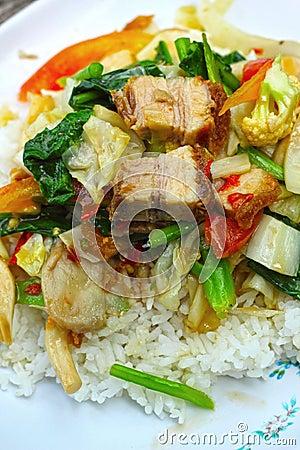 Crispy roasted  pork stir fry with vegetables and rice.