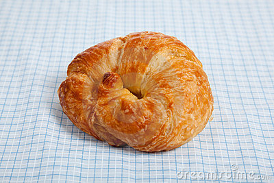 A croissant on a blue gingham tablecloth