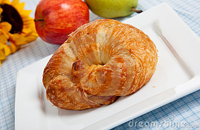 A croissant on a white plate with apples