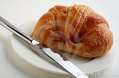 Croissant, white plate and knife