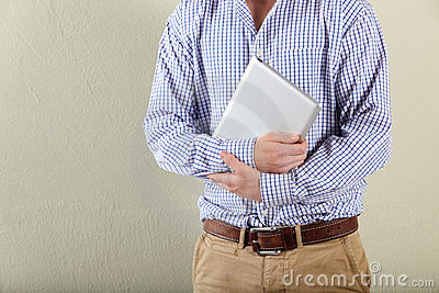 Cropped studio shot of young man holding tablet