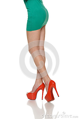 Cropped woman legs in red high heels shoes