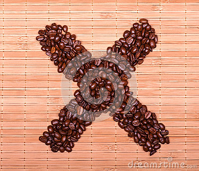 Cross of coffee beans on a decorative straw