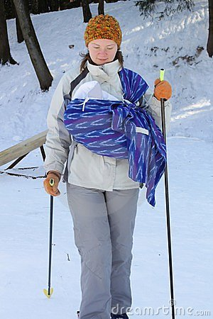 Cross contry skiing with sling and newborn baby