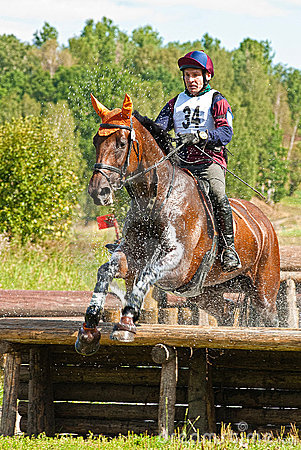 Cross-Country, horseman jumping in water drops Editorial Photo