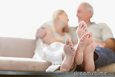 Crossed feet of a couple sitting together at home