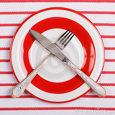 Crossed knife and fork on a red plate on striped tablecloth