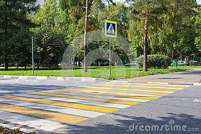 Crossroad with yellow and white stripes and road sign