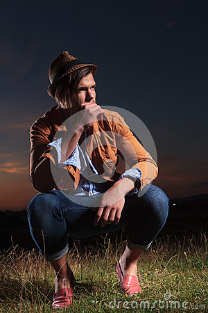 Free Crouched Casual Man Holds Straw In Mouth Royalty Free Stock Image - 33658826