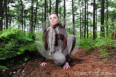 Crouching down in a forest