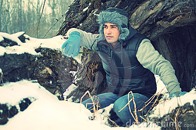 Crouching handsome young man in winter