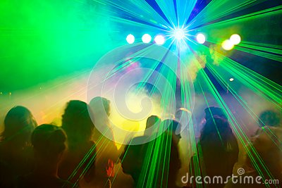 Crowd dancing under disco laser beam.