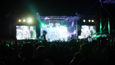 Crowd jump and dance at rock festival, arms raised of fans in bright lights of stage, excited audience waving hands. At concert, many people in colored fire of stock footage