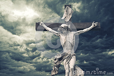 Crucifixion. Christian cross with Jesus Christ statue over storm