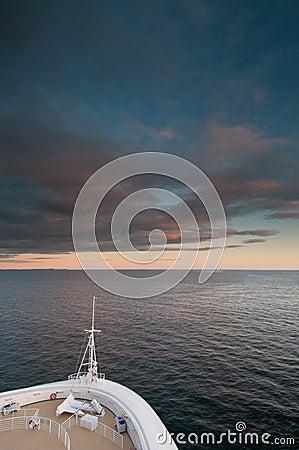 Cruise ship sailing at sunset