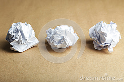 Crumpled paper ball on brown background.