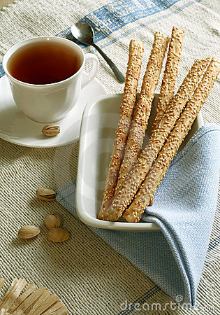 Crust sticks with sesame on plate and cup of tea