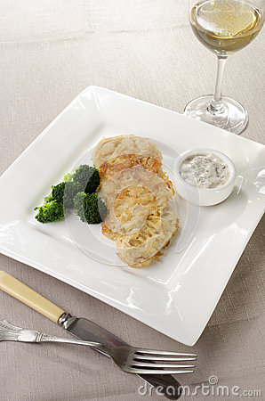 Oven baked potato crusted trout fillet with broccoli and glass of wine ...