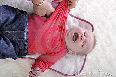 Crying baby being undressed