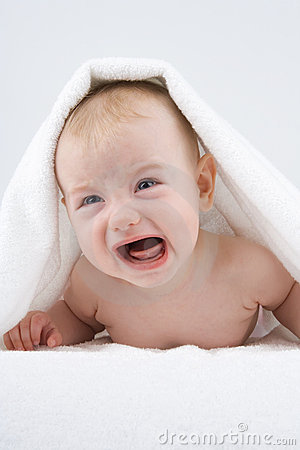 Crying baby under towel.