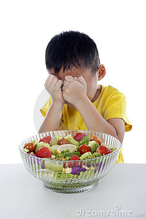 Crying boy with a bow of fruit salad