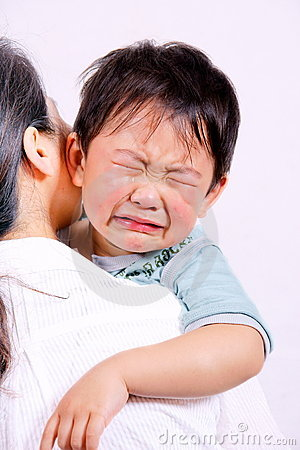 Crying boy on mother s shoulder