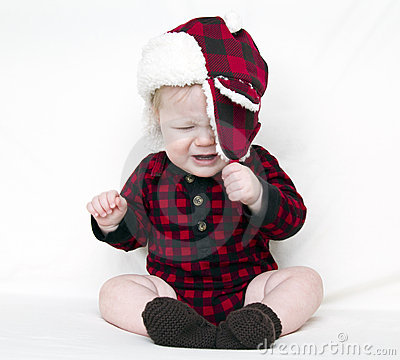 Crying Christmas baby trying to pull off hat
