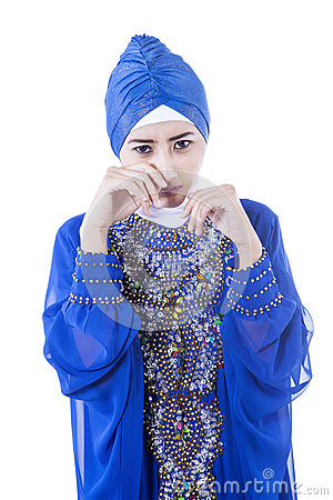 Crying female muslim in blue dress - isolated
