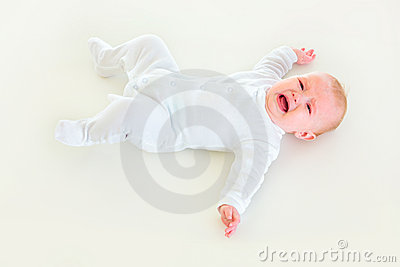 Crying four month old  baby laying on back