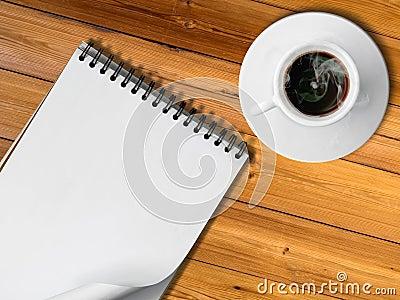 Cuaderno y taza blanca de café caliente