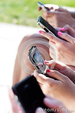 Cuatro muchachas que charlan con sus smartphones