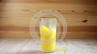 Cubo de hielo cae en un vaso con jugo naranja Movimiento lento metrajes