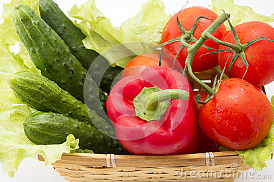 Cucumbers, tomatoes, peppers, lettuce in basket Stock Photo